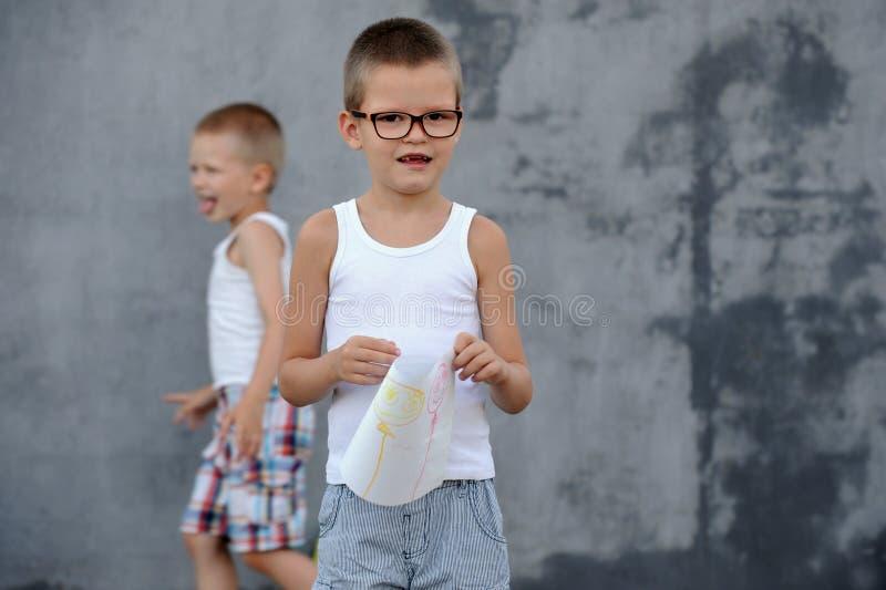 Le garçon supérieur dans une famille nombreuse va à l'école et montre ses dessins photo libre de droits