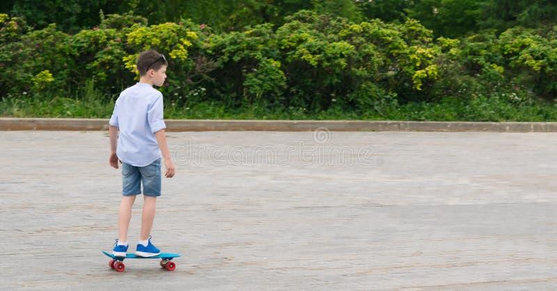 Le garçon sur des sports bleus font de la planche à roulettes, roulant sur une place en pierre, il y a un endroit pour l'inscript photo stock