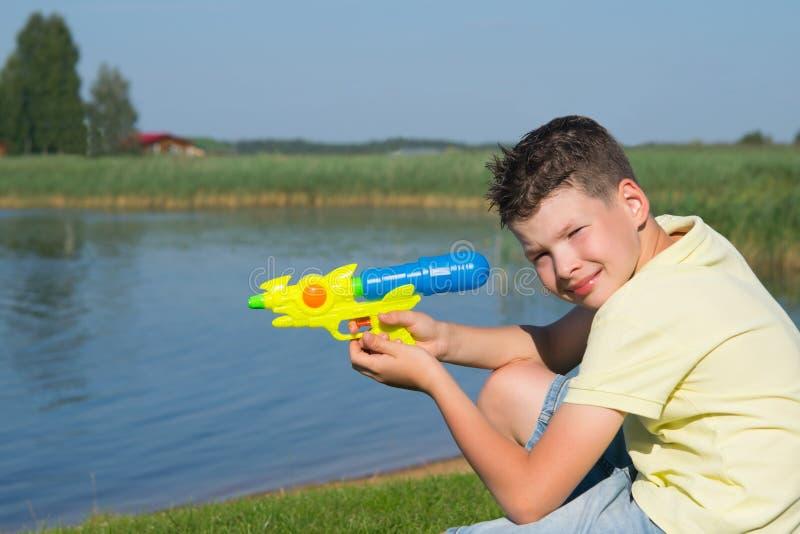 Le garçon, sur le fond d'un beau paysage, jouant avec un pistolet d'eau, plan rapproché photographie stock