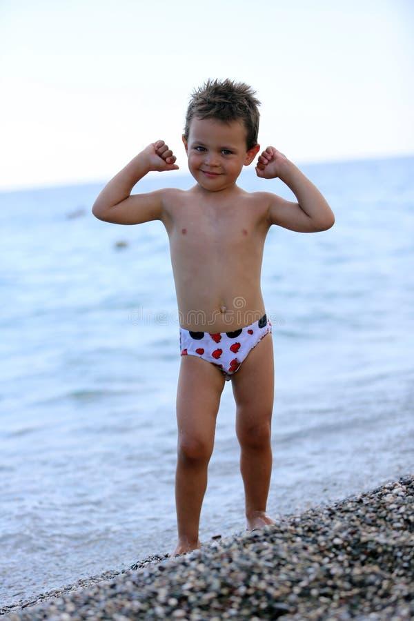 Le garçon sur la plage montre à quel point il fort est image stock