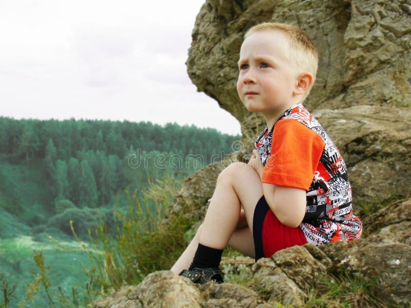 Le garçon sur la roche photo stock