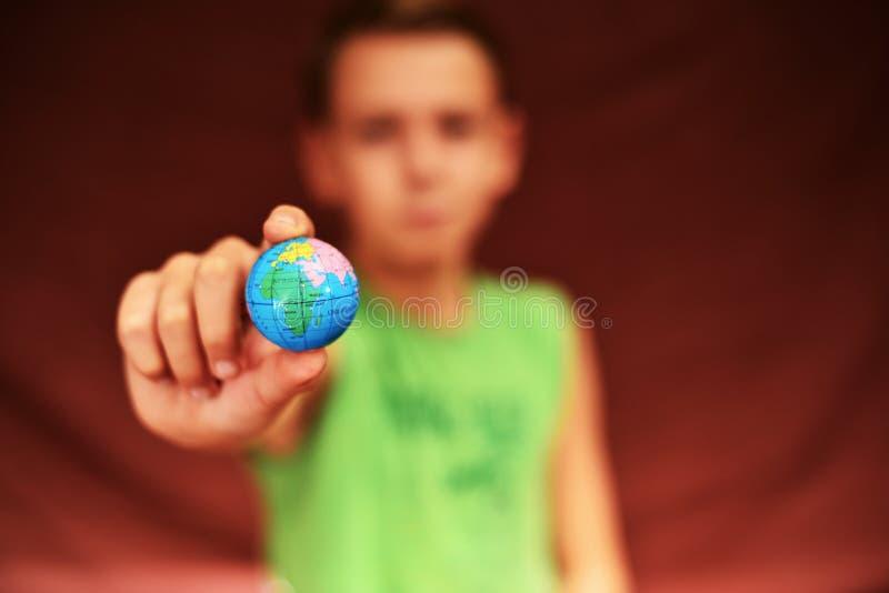 Le garçon tient la terre de planète dans des ses mains, sur un fond rouge photographie stock libre de droits