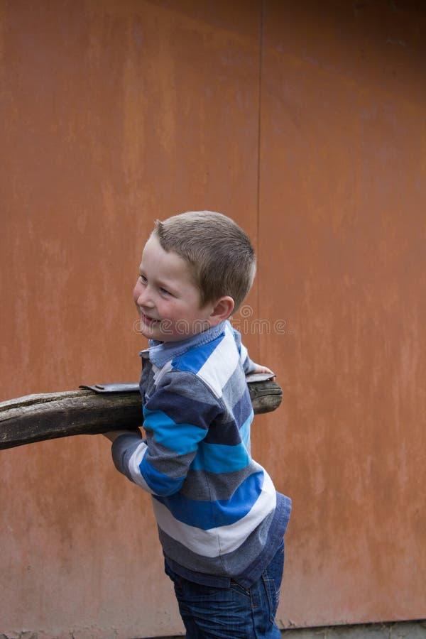 Le garçon tient les faisceaux en bois image stock