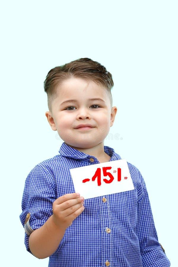 Le garçon tient un signe avec un pourcentage des remises photos stock