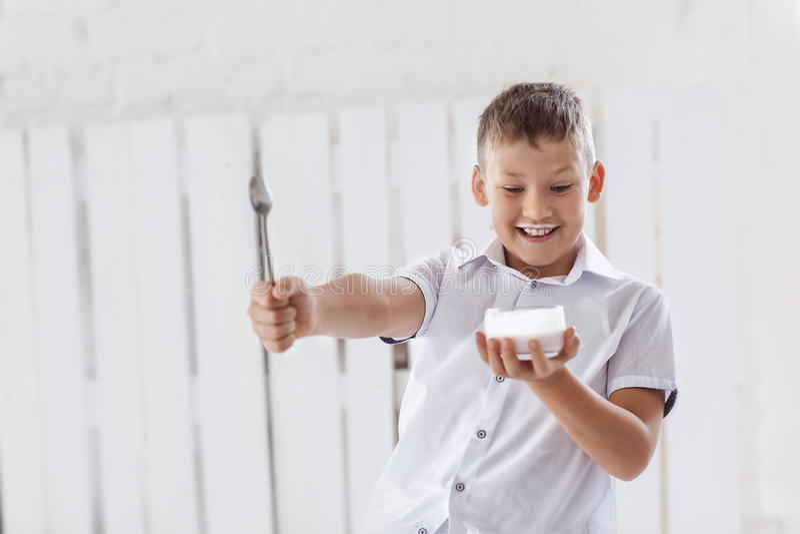 Le garçon tient une crème et une cuillère images libres de droits