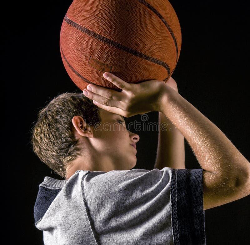 Le garçon tirant un basket-ball, se ferment  image libre de droits