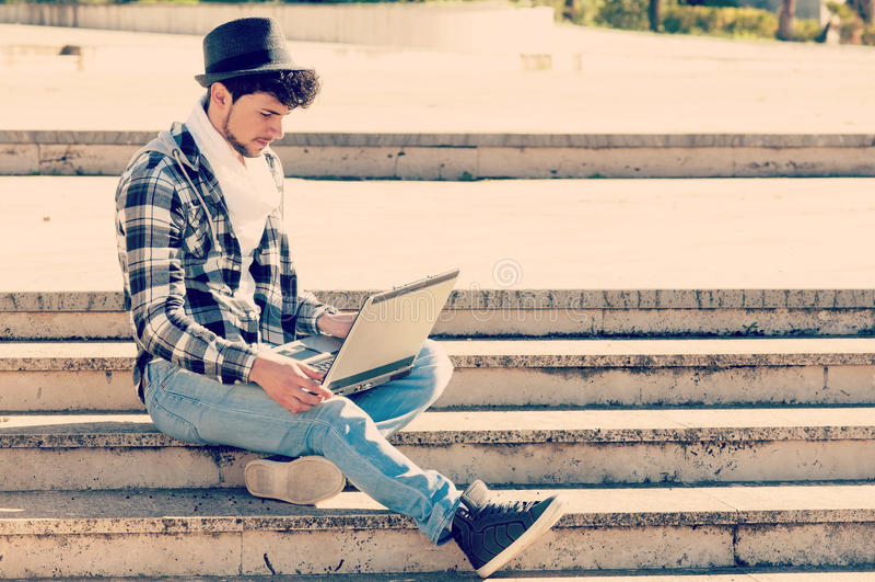 Le garçon travaillant sur son ordinateur portable avec un filtre s'est appliqué dans l'étable d'instagram images libres de droits