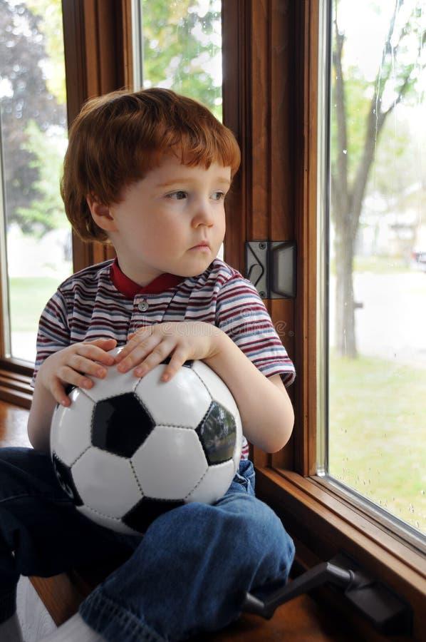 Le garçon veut jouer au football un jour pluvieux image stock