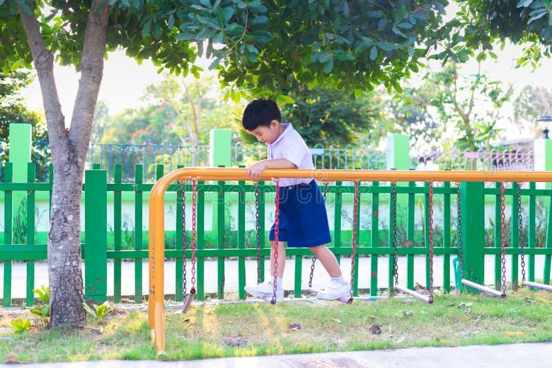 Le gar?on asiatique accrochent la barre de singe ou la barre d'?quilibre pour l'?quilibre au terrain de jeu ext?rieur photo stock
