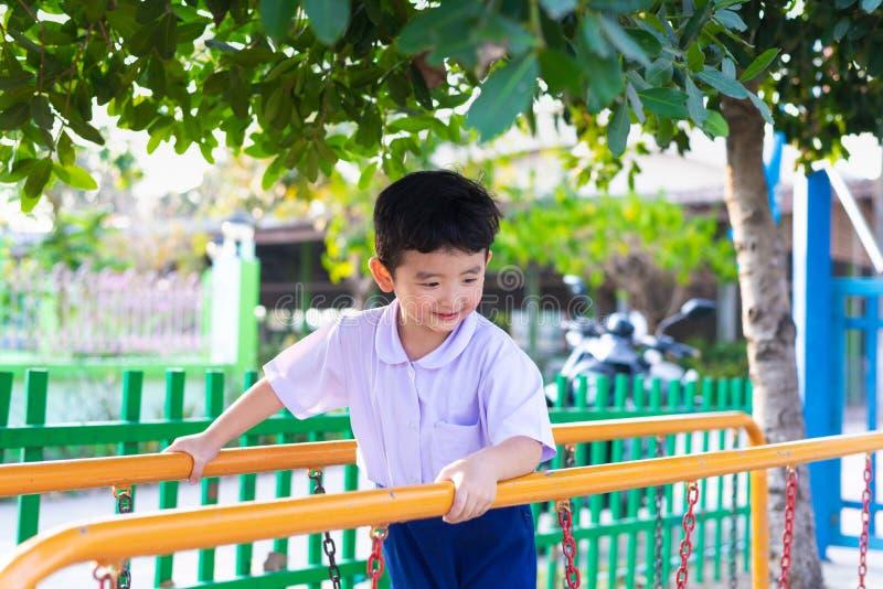 Le gar?on asiatique accrochent la barre de singe ou la barre d'?quilibre pour l'?quilibre au terrain de jeu ext?rieur images stock