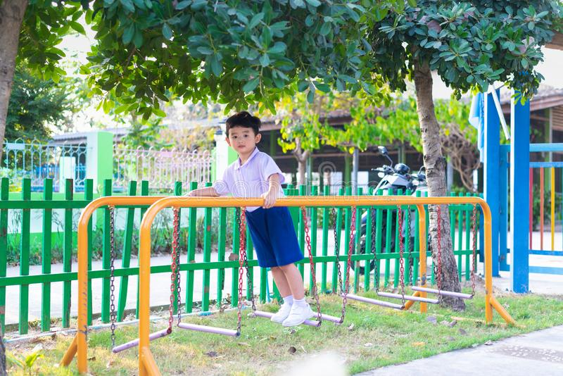 Le gar?on asiatique accrochent la barre de singe ou la barre d'?quilibre pour l'?quilibre au terrain de jeu ext?rieur photo libre de droits