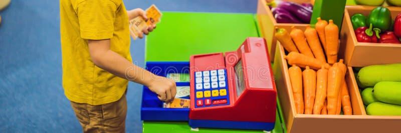 Le gar?on joue avec la caisse enregistreuse du ` s d'enfants instruction financière pour la BANNIÈRE d'enfants, LONG FORMAT images stock