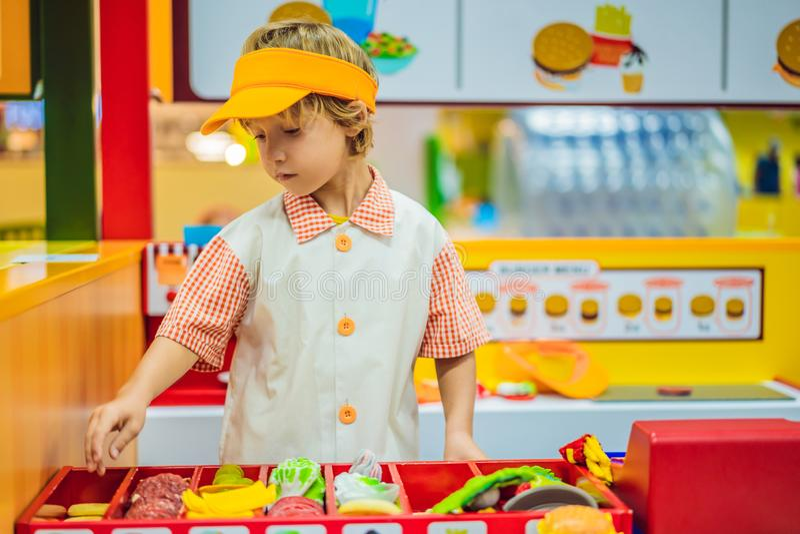 Le gar?on joue dans la cuisine de jouet, fait cuire un hamburger photographie stock