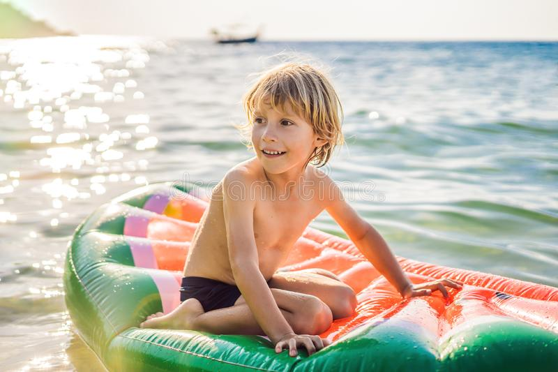 Le gar?on nage en mer sur un matelas gonflable photographie stock