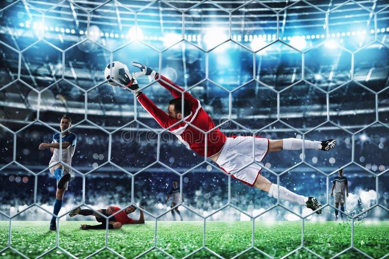 Le gardien de but attrape la boule dans le stade pendant une partie de football photos stock