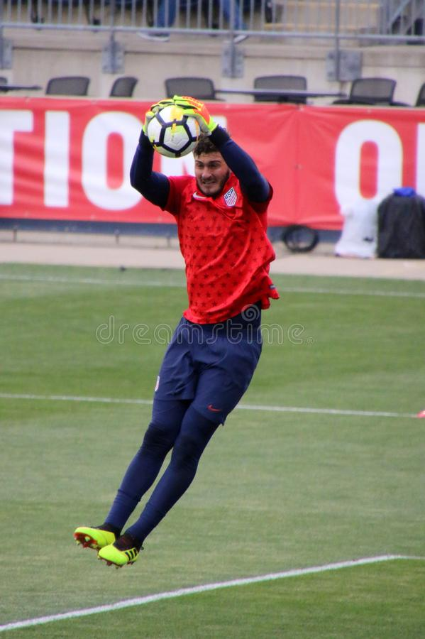Le gardien de but saute haut dans le ciel pour attraper le ballon de football photos libres de droits