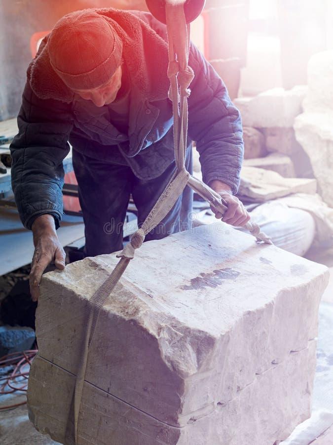 Le gemme-travailleur de sculpteur soulève une grue par morceau de marbre images libres de droits