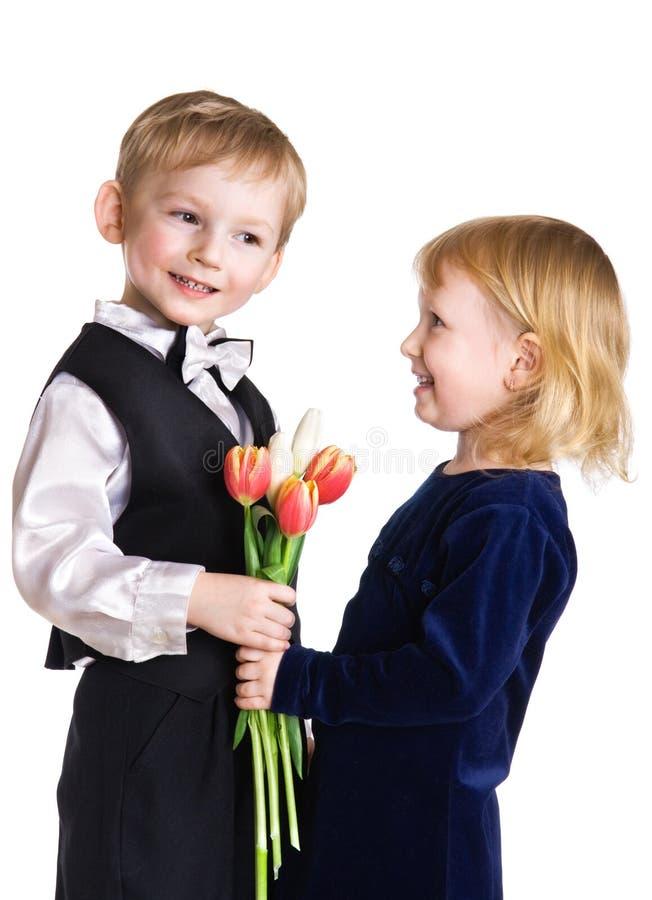 Le gentil garçon donne à la fille des tulipes images libres de droits