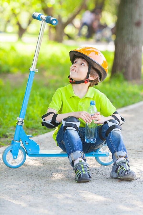 Le gentil garçon s'assied sur le scooter de coup-de-pied avec la bouteille de l'eau photographie stock libre de droits