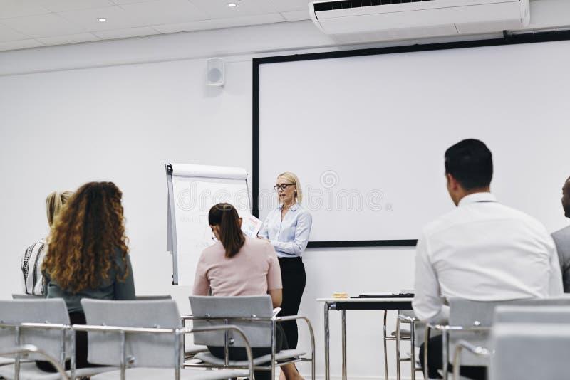 Le gestionnaire discute avec le personnel pendant la présentation photos stock