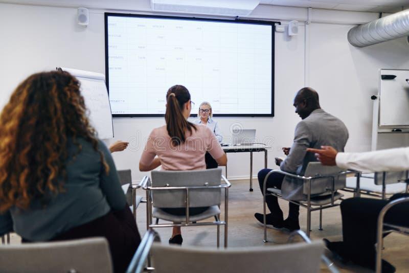 Le gestionnaire présente un écran de projection au personnel de bureau image stock