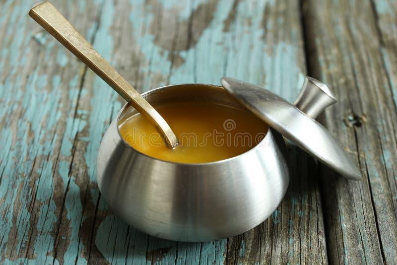 Le ghee/a clarifié le beurre sur le fond bleu rustique, foyer sélectif image libre de droits