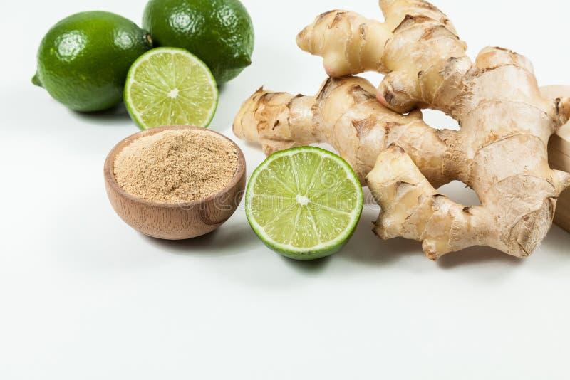 Le gingembre et les citrons s'enracinent ; photo sur le fond neutre photo libre de droits