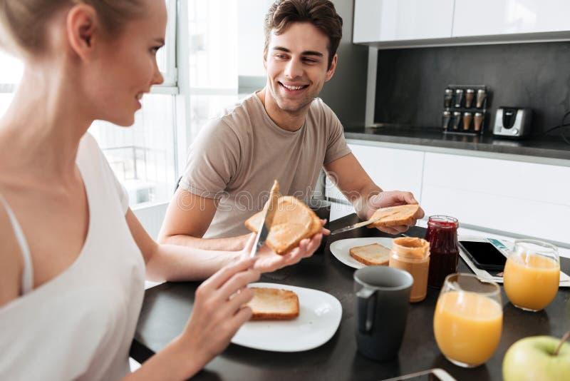 Le giovani belle coppie che si siedono nella cucina ed hanno prima colazione fotografia stock
