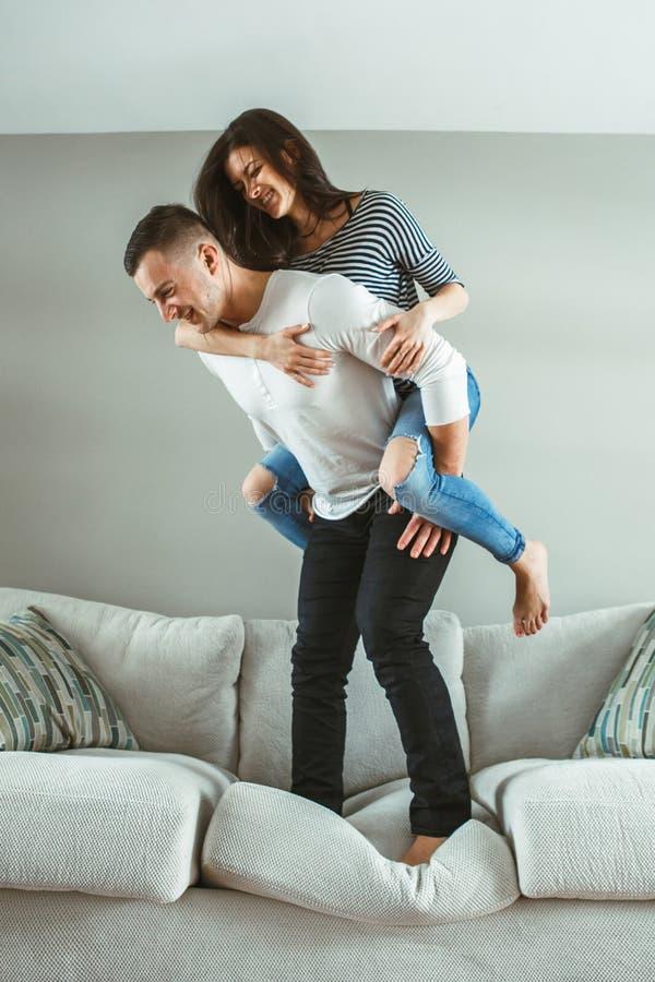 Le giovani belle coppie divertenti equipaggiano la donna nell'amore divertendosi il salto dal letto all'interno a casa fotografia stock libera da diritti