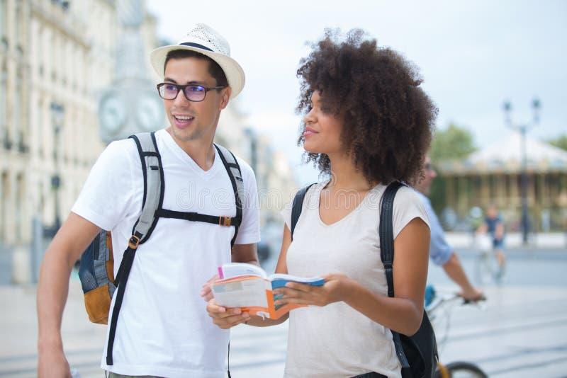 Le giovani belle coppie romantiche felici hanno perso in città fotografia stock