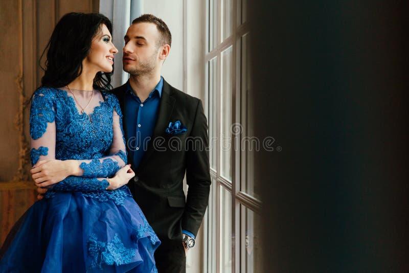 Le giovani belle coppie splendide alla moda ad una data dalla finestra in un ristorante mandano in aria lo studio fotografie stock libere da diritti