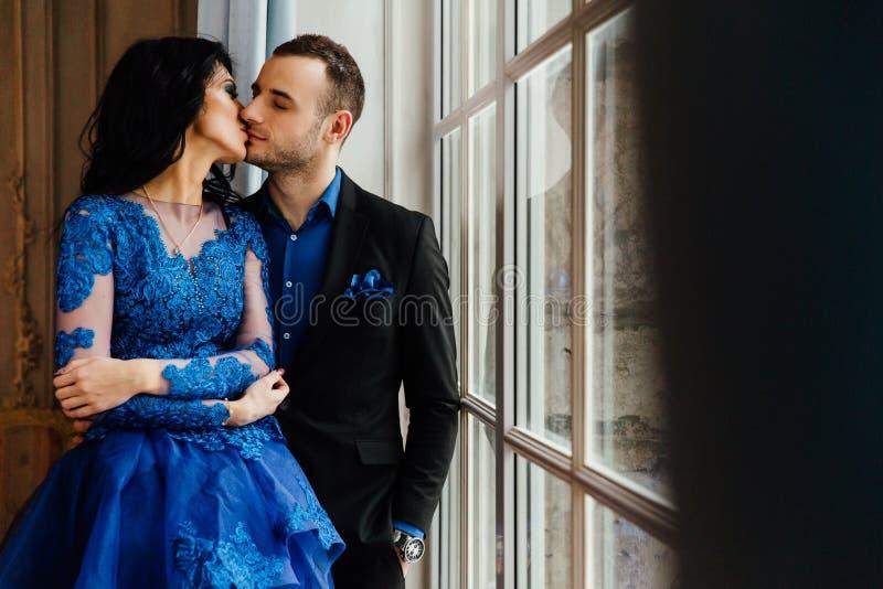 Le giovani belle coppie splendide alla moda ad una data dalla finestra in un ristorante mandano in aria lo studio fotografie stock