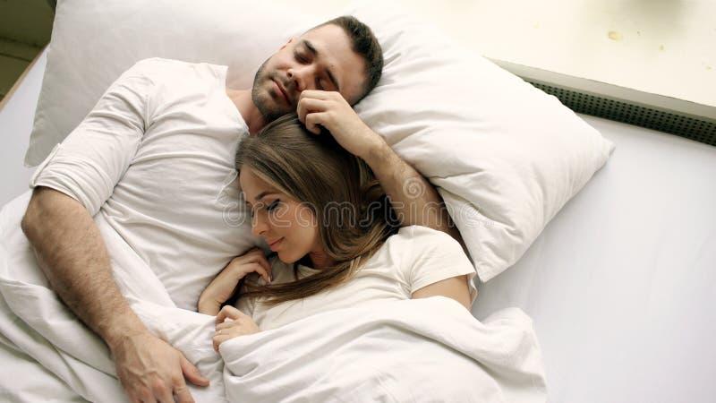 Le giovani belle e coppie amorose baciano ed abbracciano nel letto mentre svegliano di mattina Punto di vista superiore dell'uomo immagine stock