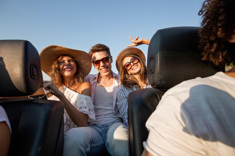 Le giovani brune incantanti in cappelli stanno sedendo con il giovane in un cabriolet nero e stanno sorridendo un giorno di estat fotografia stock libera da diritti