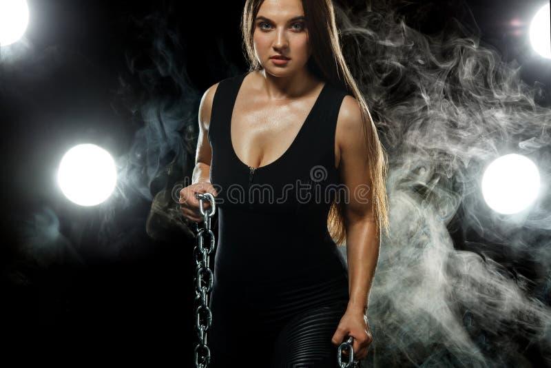 Le giovani catene attraenti della tenuta dell'atleta e del culturista della donna di forma fisica su fondo nero con colore fumano fotografia stock