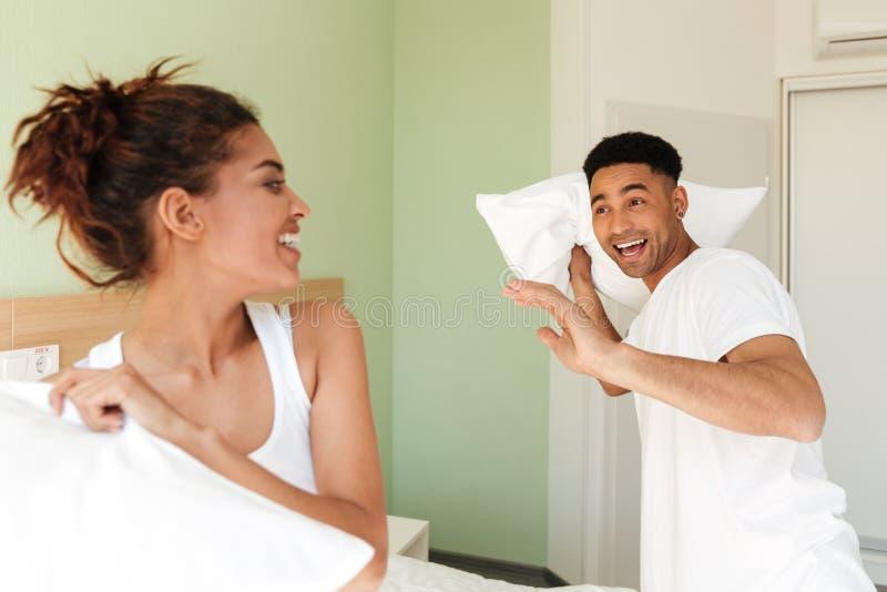 Le giovani coppie amorose africane felici si divertono all'interno fotografia stock