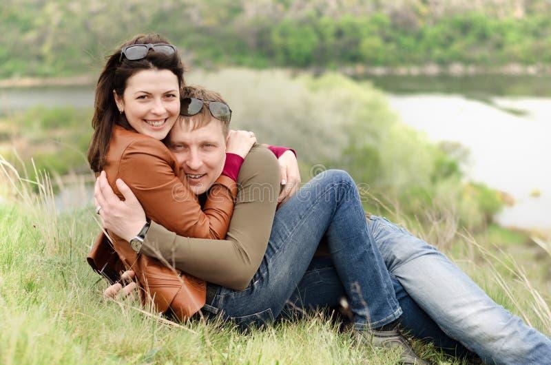 Le giovani coppie amorose che abbracciano su una collina completano immagini stock libere da diritti