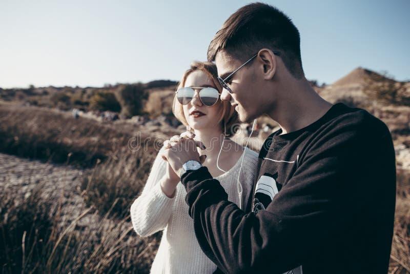 Le giovani coppie amorose degli adolescenti in occhiali da sole si tengono per mano e Li fotografia stock
