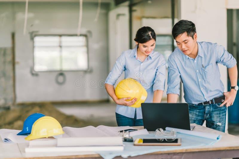 Le giovani coppie asiatiche dell'ingegnere lavorano insieme facendo uso del computer portatile al sito della costruzione di edifi immagine stock