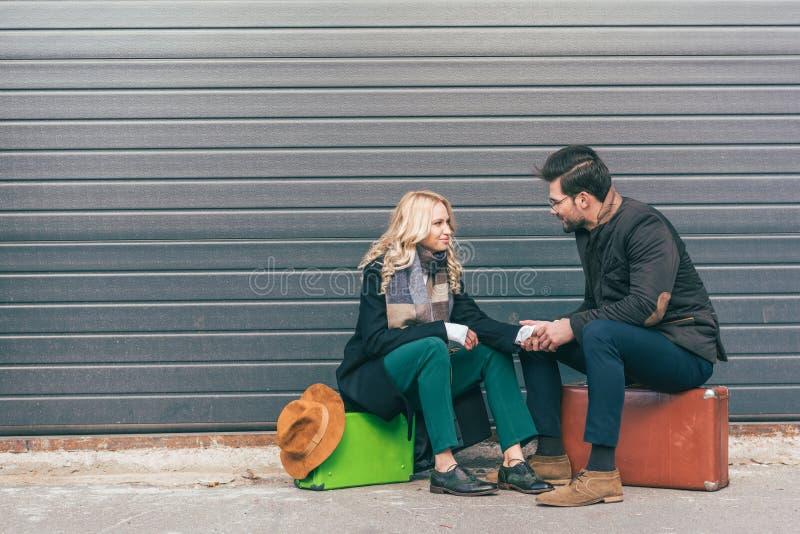 le giovani coppie in autunno equipaggiano la seduta sulle valigie e sorridere ciascuno fotografia stock