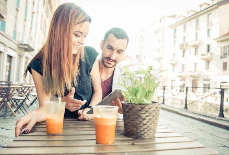 Le giovani coppie che bevono un vegano scuotono in una barra fotografia stock libera da diritti