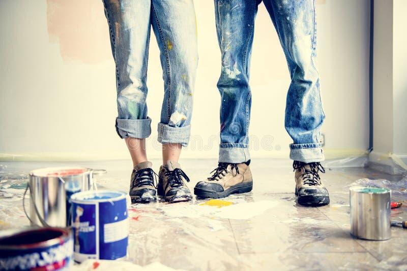 Le giovani coppie che dipingono una parete si dirigono il concetto del rinnovamento immagini stock