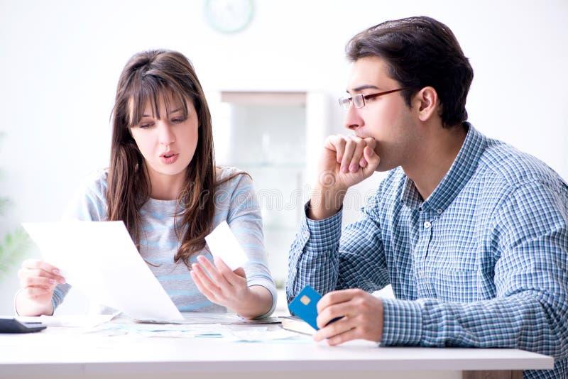 Le giovani coppie che esaminano la famiglia finanziano le carte fotografia stock