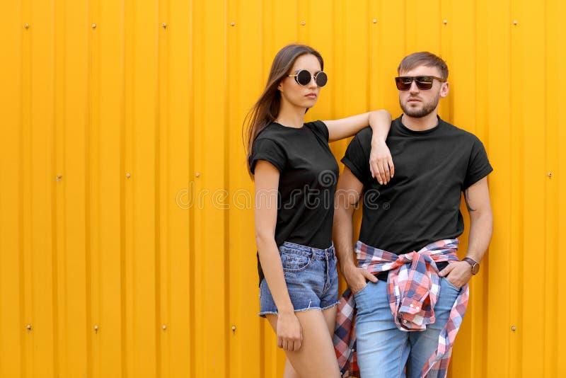 Le giovani coppie che portano le magliette nere si avvicinano alla parete di colore immagine stock