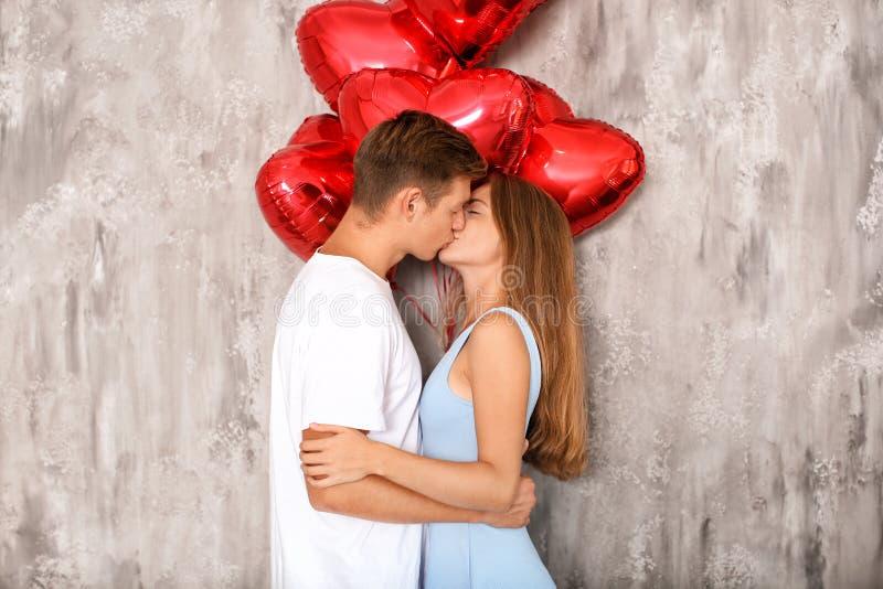 Le giovani coppie con cuore hanno modellato i palloni rossi che baciano vicino alla parete grigia fotografia stock