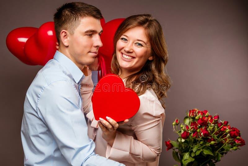 Le giovani coppie con cuore hanno modellato i palloni rossi vicino alla parete grigia fotografia stock