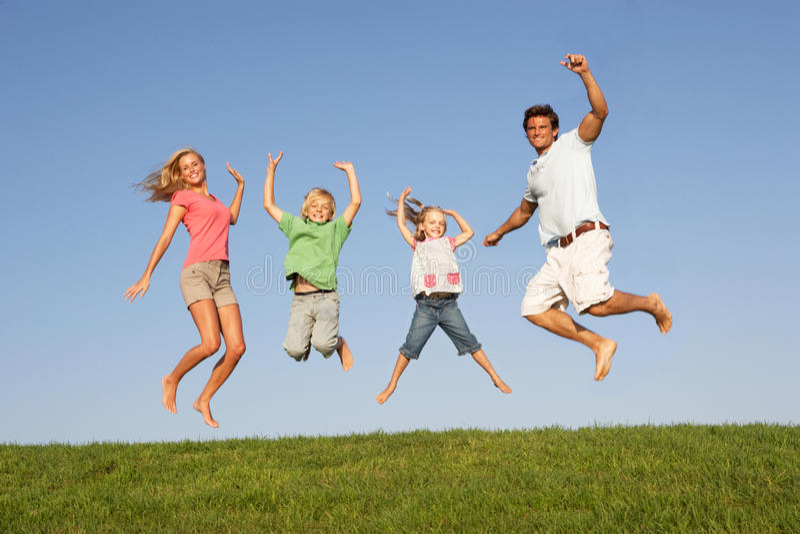 Le giovani coppie con i bambini saltano in un campo fotografie stock