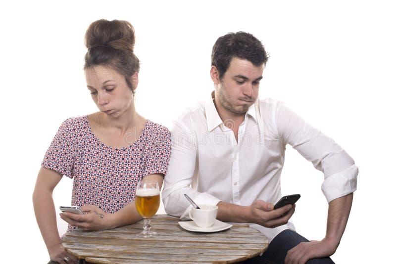 Le giovani coppie con i loro telefoni sono contrariate immagine stock libera da diritti