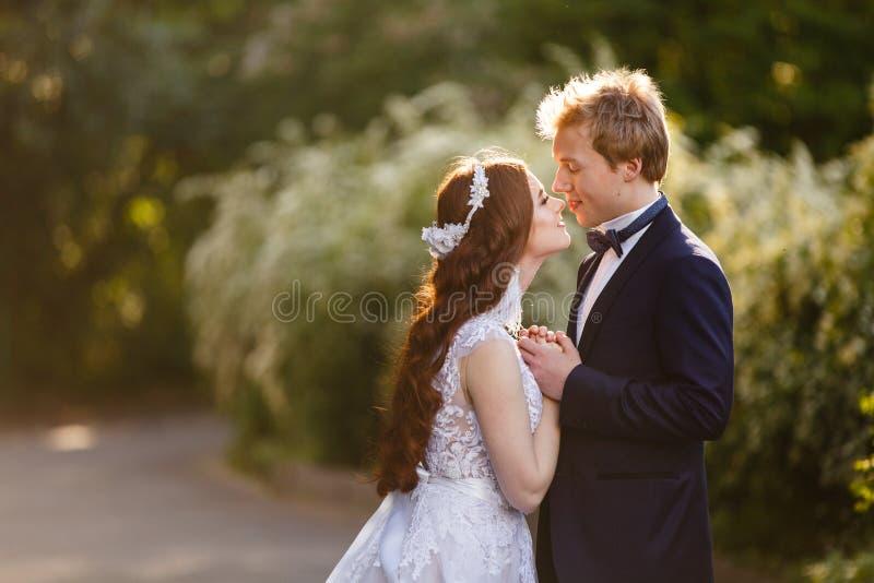 Le giovani coppie dello sposo e della sposa in una fioritura fanno il giardinaggio fotografie stock