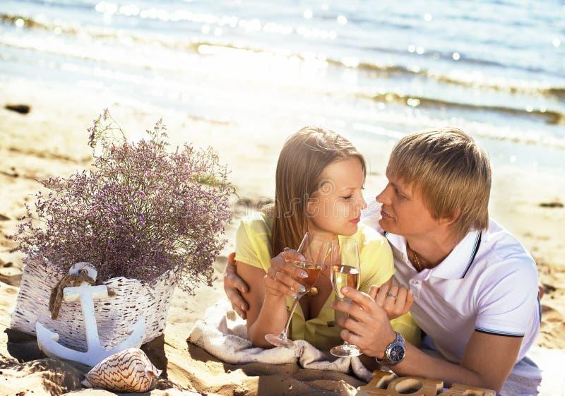 Le giovani coppie felici che godono del picnic sulla spiaggia ed hanno buon Ti immagini stock